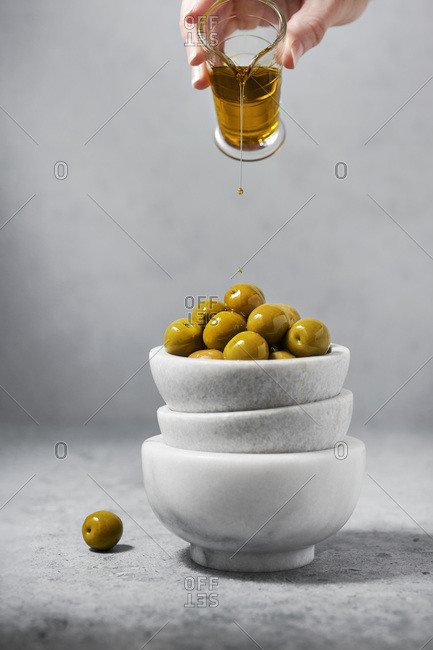 Marble bowls filled with green olives being drizzled with olive oil by a woman's hand. Gray background and surface.