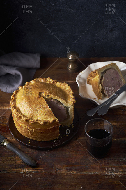 Traditional British raised pork pie with bacon and herbs with one slice cut and served next to a glass of red wine