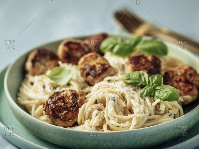 Zucchini Parmesan Meatballs with Pasta Carbonara in green plate over blue linen tablecloth. Close up view of creamy carbonara with beef meatballs.
