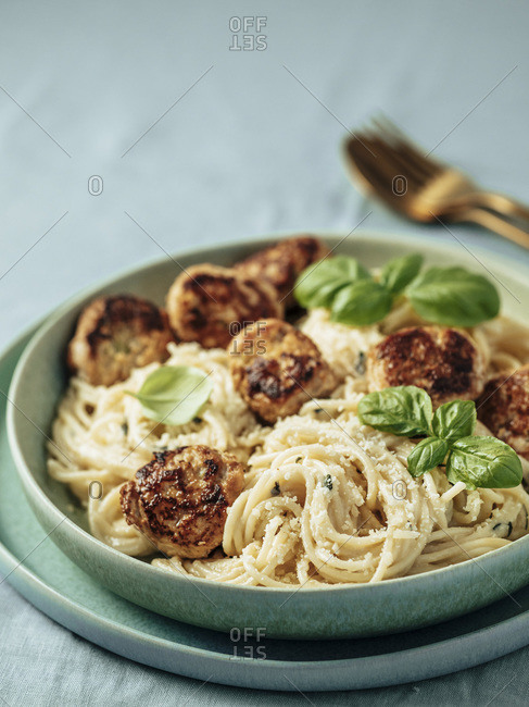 Zucchini Parmesan Meatballs with Pasta Carbonara in green plate over blue linen tablecloth.