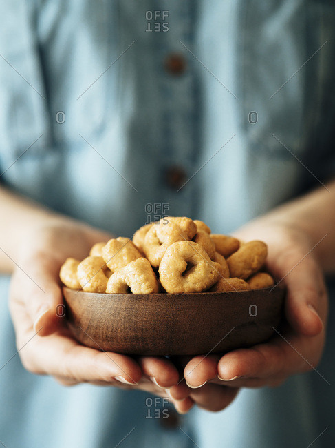 Traditional Italian snack taralli or tarallini in wooden bowl in female hands. Unrecognizable woman in blue jeans shirt holds tarallini.
