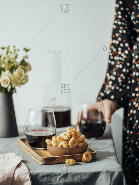 Traditional Italian snack taralli or tarallini with red wine on the table in interior. Unrecognizable woman in festive dress takes glass tumbler with red wine.