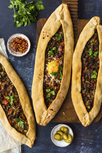 Turkish pide stuffed with beef and an egg on a wooden board and on the ground accompanied by crushed chilies, pickles and parsley photographed on a dark background.