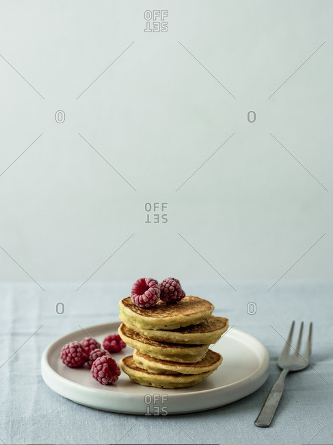 Gluten-free zucchini pancakes topped with raspberries