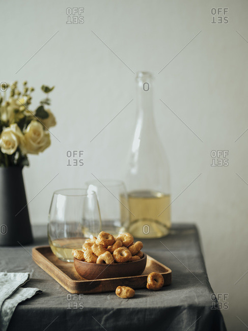 Traditional Italian snack taralli or tarallini with white wine on the table covered gray linen tablecloth.