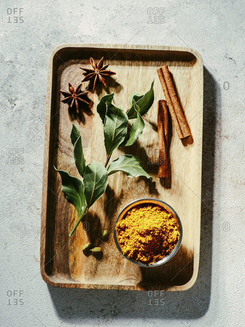 Indian or Pakistani masala powder and spices on wooden tray.