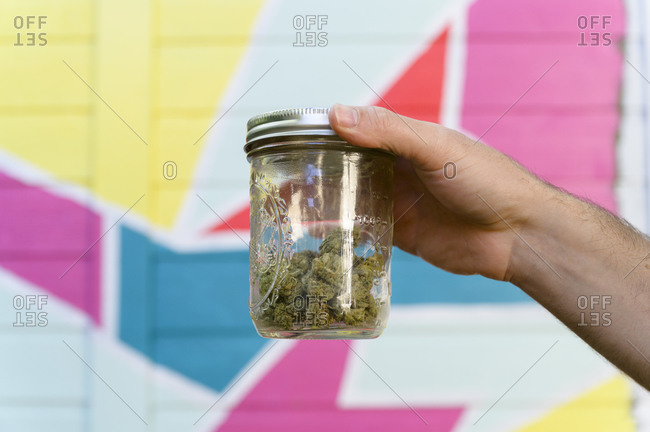 Close-up of mans hand holding jar with cannabis buds in front of colorful mural