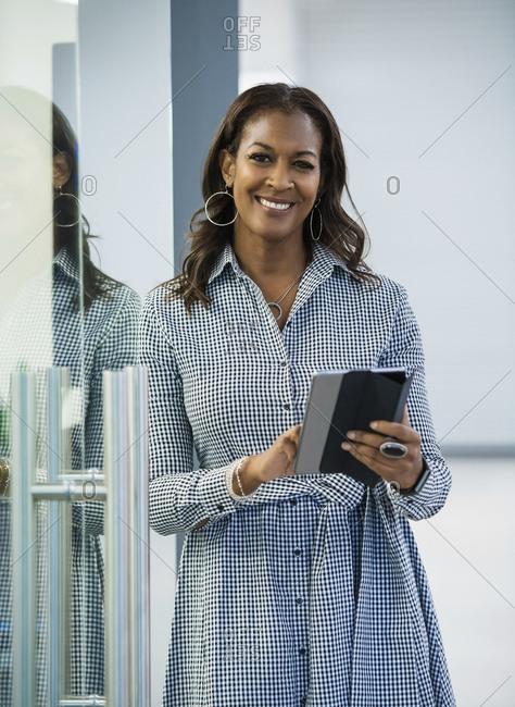 Portrait of smiling businesswoman with digital tablet in office