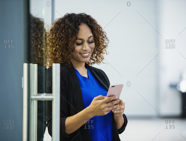 Smiling businesswoman using smart phone in office