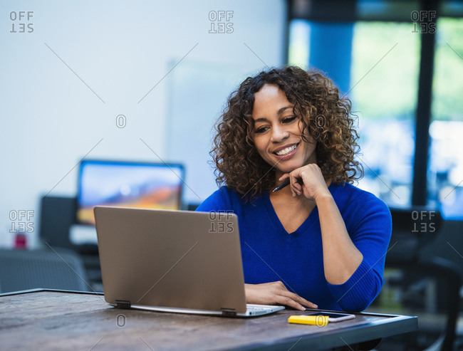 Smiling woman looking at laptop at desk in office