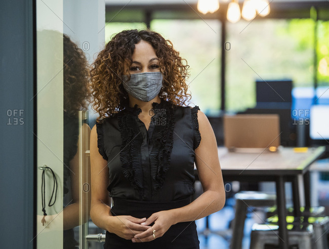Portrait of woman in face mask standing in office