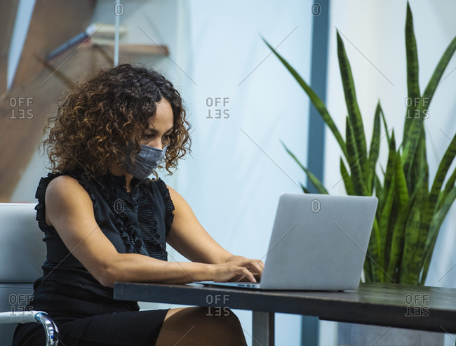 Businesswoman wearing face mask working on laptop at desk in office