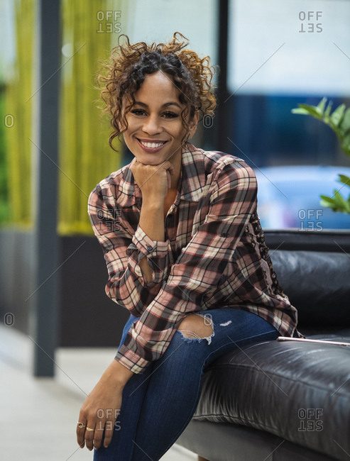 Portrait of smiling woman sitting on sofa in office