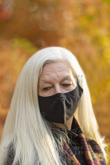 Portrait of senior woman wearing Covid protective mask outdoors in fall