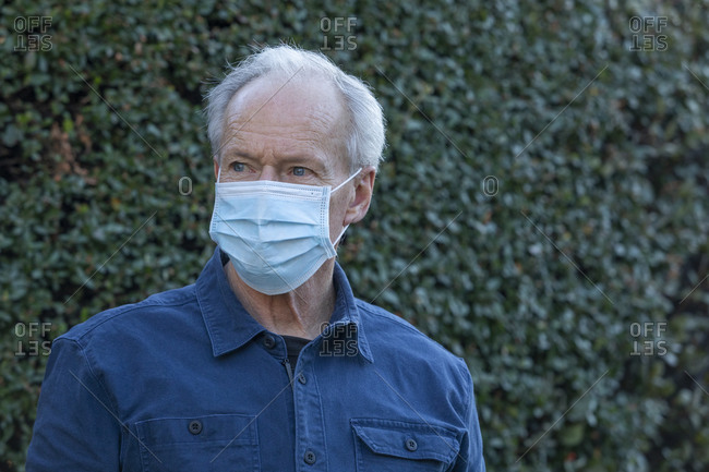 Outdoor portrait of senior man wearing covid protective mask outside in fall