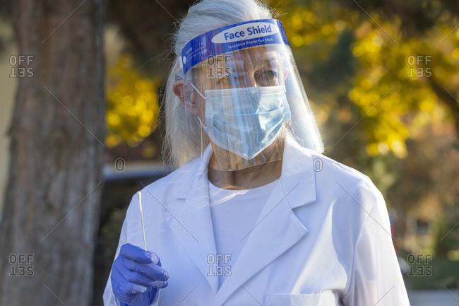 Female medical staff in protective clothing holding coronavirus swab test outdoors