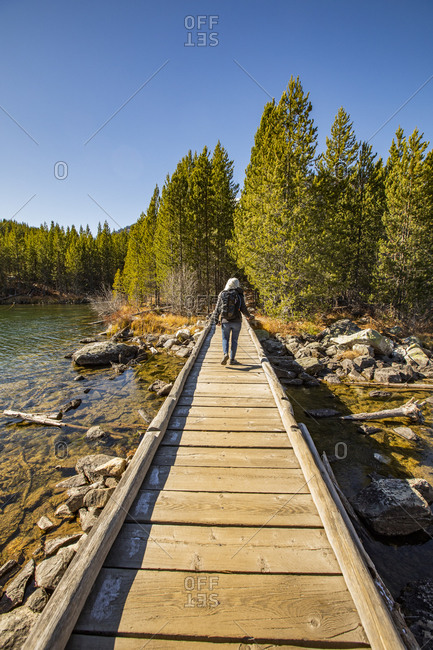 USA, Wyoming, Jackson, Grand Teton National Park, Senior woman walking on wooden path over Taggart Lake in Grand Teton National Park