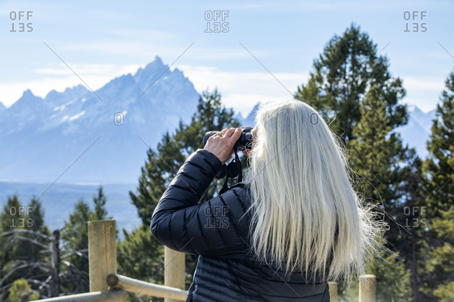 USA, Wyoming, Jackson, Grand Teton National Park, Senior woman looking through binoculars at landscape in Yellowstone National Park