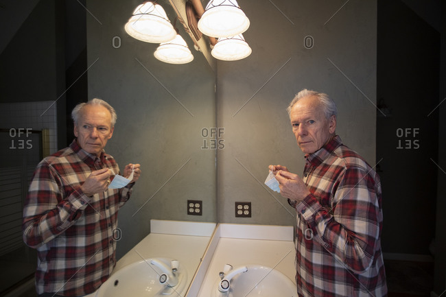 Senior man holding Covid protective mask in front of mirror in bathroom