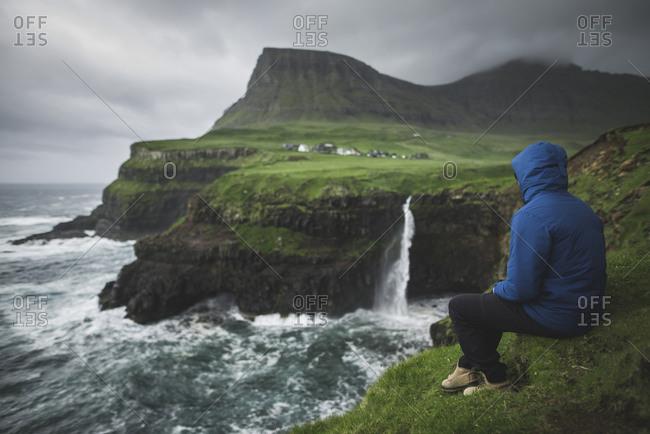 Denmark, Faroe Islands, Gasadalur Village, Mt. Lafossur Waterfall, Man sitting on edge of cliff and looking at Mulafossur Waterfall