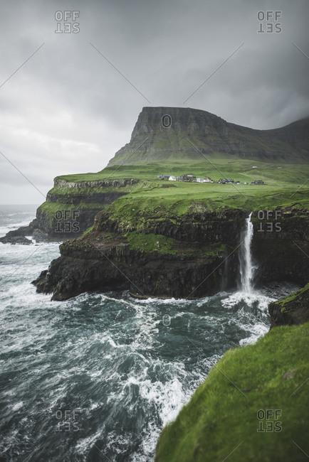 Denmark, Faroe Islands, Gasadalur Village, Mt. Lafossur Waterfall, Coastline with Mulafossur Waterfall falling into Atlantic Ocean