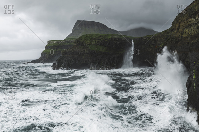 Denmark, Faroe Islands, Gasadalur Village, Mt. Lafossur Waterfall, Coastline with Mulafossur Waterfall falling into Atlantic Ocean in stormy day