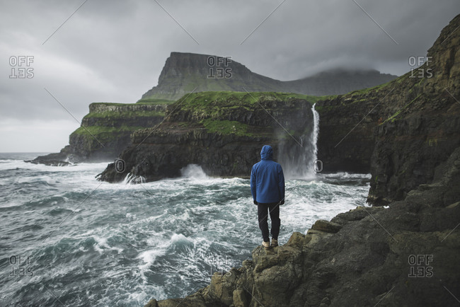 Denmark, Faroe Islands, Gasadalur Village, Mt. Lafossur Waterfall, Man standing on cliff and looking at Mulafossur Waterfall day during storm