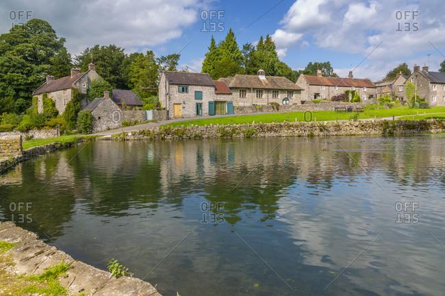 View of cottages reflecting in village pond, Tissington, Peak District National Park, Derbyshire, England, United Kingdom, Europe
