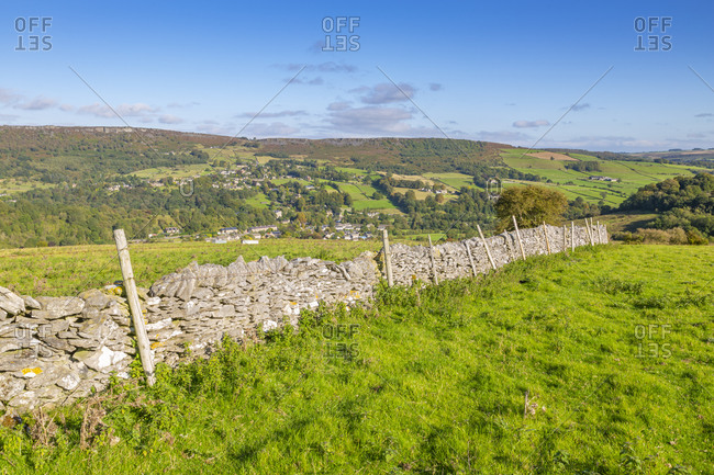 View of dry stone wall and Calver Village overlooked by Curbar Edge, Calver, Derbyshire Peak District, Derbyshire, England, United Kingdom, Europe