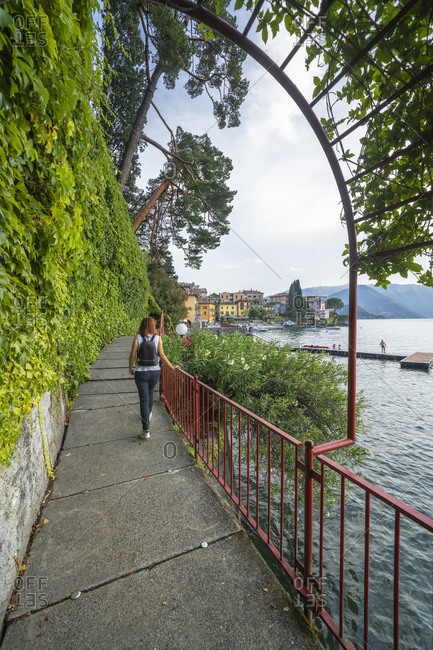 Woman walking on famous lovers' promenade on lakeside of Varenna, Lake Como, Lecco province, Lombardy, Italian Lakes, Italy, Europe