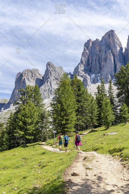 Hikers walking on the Adolf Munkel trail at foot of the Odle, Val di Funes, South Tyrol, Dolomites, Italy, Europe