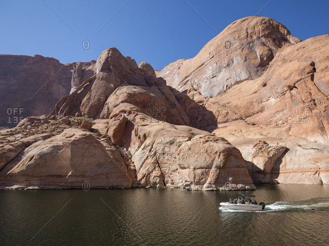 Small pleasure boat in Forbidding Canyon, a narrow arm of Lake Powell, Glen Canyon National Recreation Area, Utah, United States of America, North America