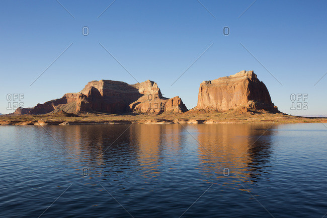 Sandstone cliffs reflected in the tranquil waters of Lake Powell, Glen Canyon National Recreation Area, Utah, United States of America, North America