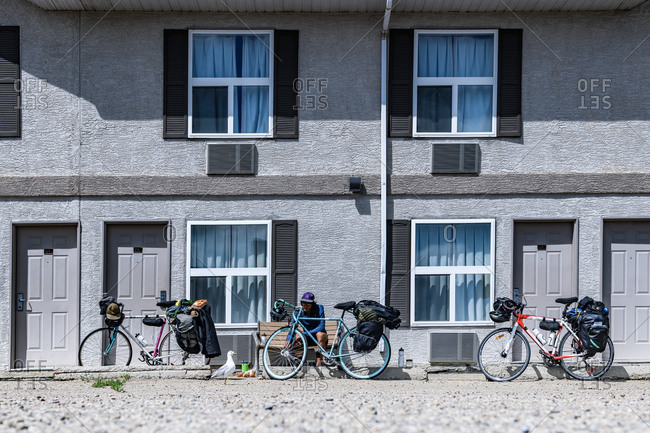 Cyclist with bikes outside building, Ontario, Canada