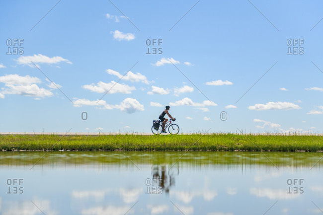 Cyclist riding past water, Ontario, Canada