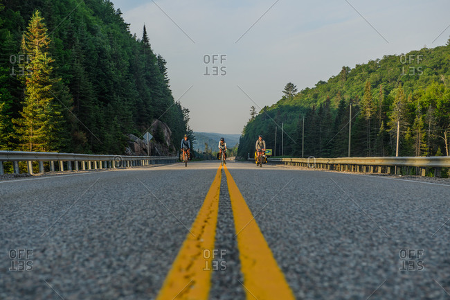 Three cyclists on road, Ontario, Canada