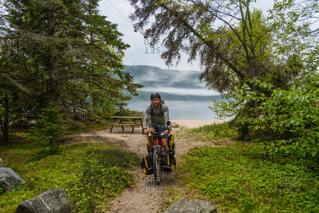 Cyclist with bike at scenic stop on travels, Ontario, Canada