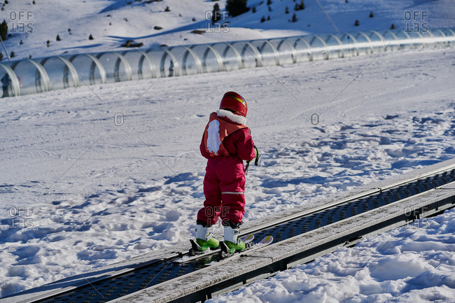 Child on conveyor belt ski lift, Formigal ski resort, Spain