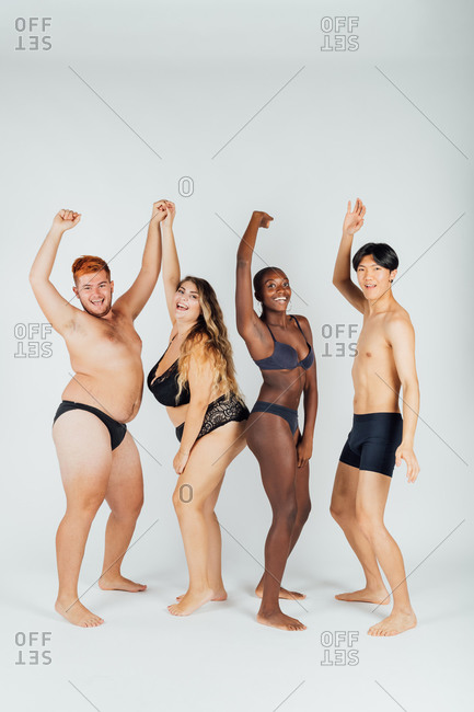 Group of young people wearing underwear, arms raised