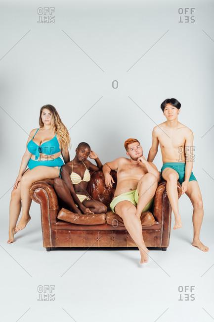Young people on sofa, wearing underwear and swimwear