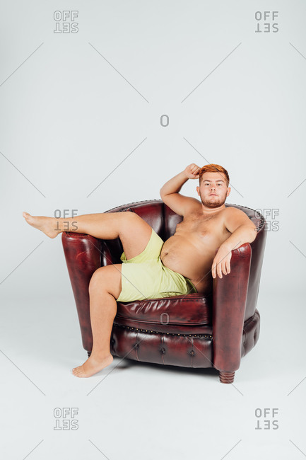 Portrait of confident young man in armchair with leg raised
