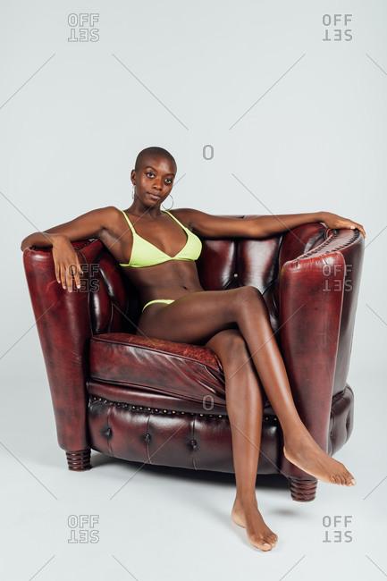 Portrait of young woman, sitting in chair, wearing bikini