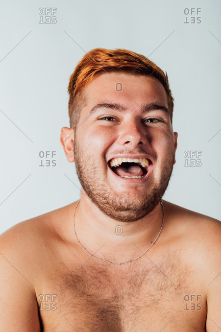 Portrait of a young man with bare chest, laughing