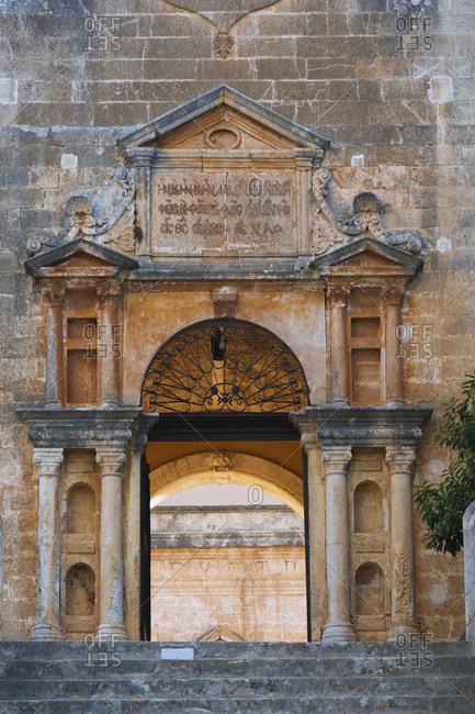 April 28, 2016: Stone steps and arched entrance with Doric columns at Holy Trinity (Agia Triada) Monastery, Akrotiri Peninsula, Chania region, Crete Island, Greece