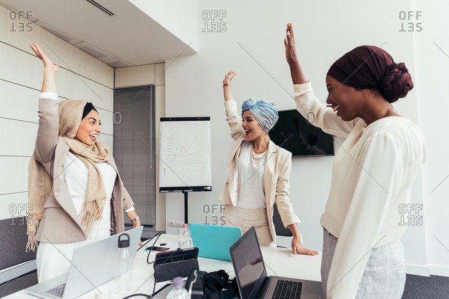 Businesswomen raising their arms together