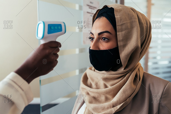 Woman getting her temperature checked