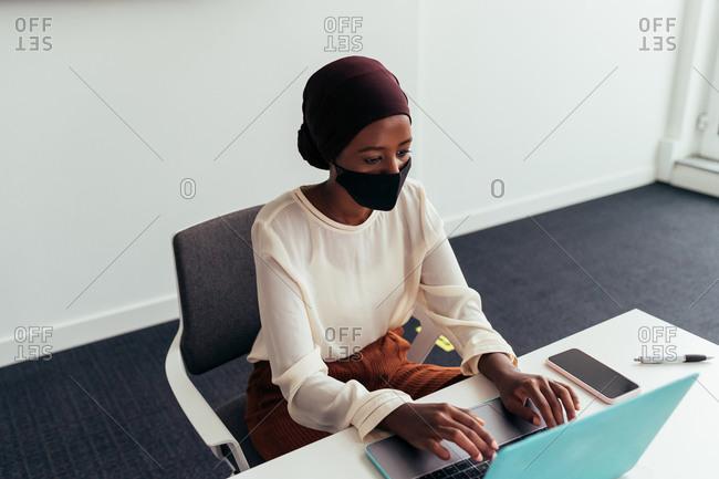 Woman working on laptop, wearing face mask