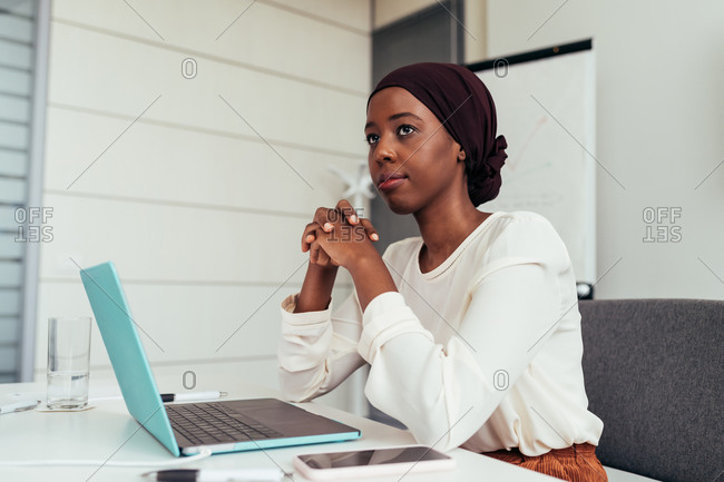 Businesswoman in office with laptop, thinking