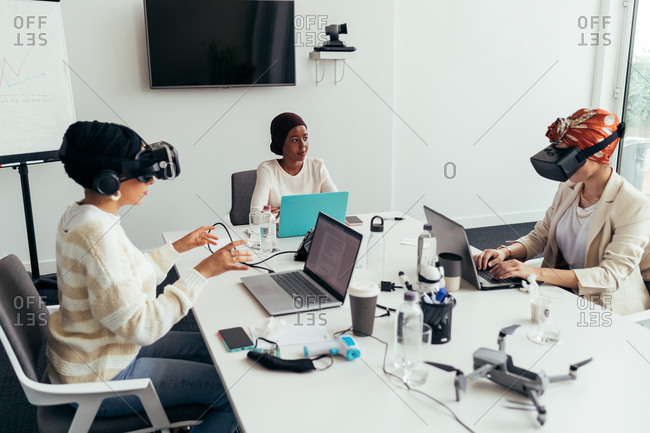 Colleagues using virtual reality headsets in office