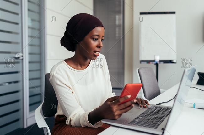 Businesswoman using smartphone and laptop